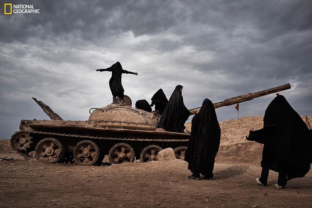 """Yanan Li / """"Overlooking Iraq from Iran""""  Un gruppo di studentesse iraniane gioca intorno ad un carro armato abbandonato.  Shalamcheh, Khuzestan, Iran."""