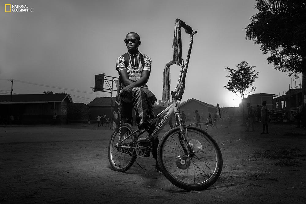 """Joel Nsadha / """"At The Play Ground"""" Bwengye vive in uno slum, l'unico suo avere è una bicicletta e ogni sera guarda i bambini giocare a calcio.  Kampala, Central Region, Uganda."""